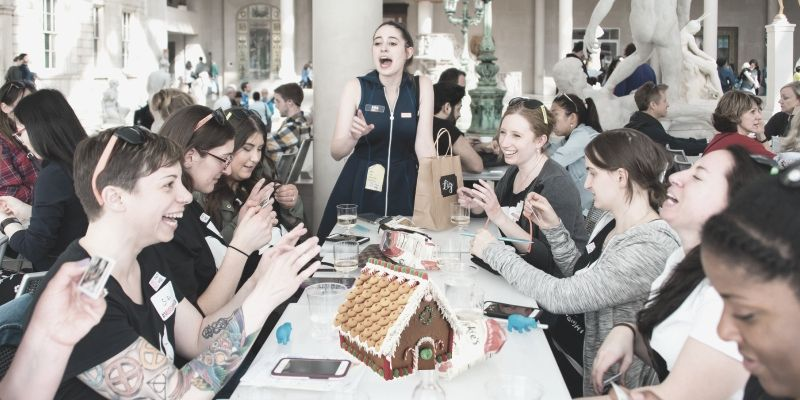 A group of young adults doing a gingerbread team bonding activity together.
